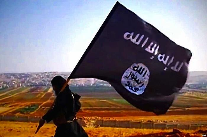 Un soldat transportant un drapeau de l'État Islamique, ou Daesh. Photo via Wikimedia Commons.