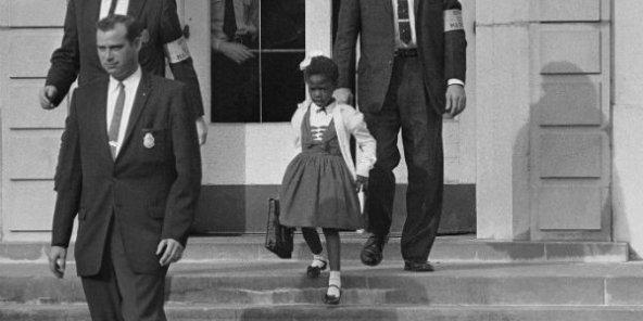 Des policiers fédéraux escortent Ruby Bridges, alors âgée de six ans, face à une foule raciste opposée à son entrée dans une école blanche, le 14 novembre 1960. © Anonymous/AP/SIPA